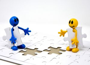 Teamwork: two cartoons working on a puzzle